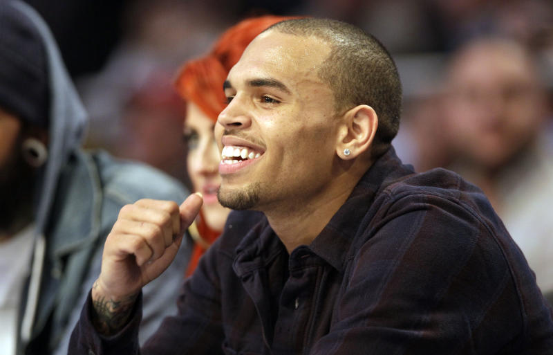 In this Feb. 26, 2012 photo, singer Chris Brown sits on the sidelines during the second half of the NBA All-Star basketball game in Orlando, Fla. New York City police are investigating an early morning Manhattan bar brawl involving hip hop stars Drake and Chris Brown. Police say five people were injured in the fight at club W.I.P. early Thursday, June 14, 2012, where people from both entourages were tossing bottles. Police say the injuries were mostly minor lacerations.(AP Photo/Chris O'Meara)
