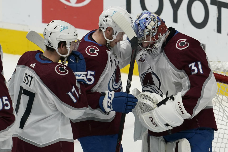 Colorado Avalanche center Tyson Jost, left, celebrates with right wing Logan O'Connor and goaltender Philipp Grubauer, right, after the Avalanche defeated the San Jose Sharks in an NHL hockey game in San Jose, Calif., Wednesday, March 3, 2021. (AP Photo/Jeff Chiu)