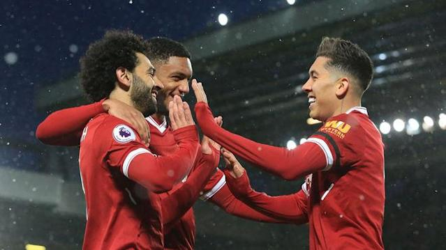 Liverpool's Brazilian midfielder Roberto Firmino (R) celebrates with Liverpool's Egyptian midfielder Mohamed Salah (L), scoring the team's third goal during the English Premier League football match between Liverpool and Watford at Anfield in Liverpool, north west England on March 17, 2018. / AFP PHOTO / PAUL ELLIS / RESTRICTED TO EDITORIAL USE. No use with unauthorized audio, video, data, fixture lists, club/league logos or 'live' services. Online in-match use limited to 75 images, no video emulation. No use in betting, games or single club/league/player publications. / (Photo credit should read PAUL ELLIS/AFP/Getty Images)