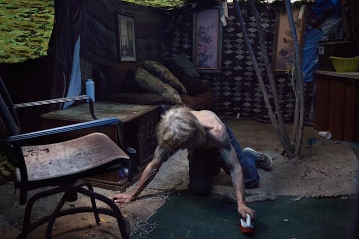 "Alan Fagerson, 54, cleans the floor of his home, dubbed the ""homeless mansion,"" in Lake Balboa in November 2016. Fagerson, originally from San Bernardino, moved to the San Fernando Valley when he was 19 and had recently finished a 15-year prison sentence. A leader of a nearby homeless encampment later evicted him from the structure, which Fagerson had made out of wood and found materials and had a guest room and a bathroom. <span class=""copyright"">(Ivan Kashinsky / For The Times)</span>"
