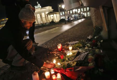 A man places a candle to pay tribute to victims in front of the Brandenburg Gate at the French embassy at Pariser Platz in Berlin January 7, 2015, following a shooting by gunmen at the offices of weekly satirical magazine Charlie Hebdo in Paris. REUTERS/Fabrizio Bensch