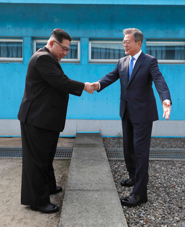 <p>North Korean leader Kim Jong Un, left, shakes hands with South Korean President Moon Jae-in over the military demarcation line at the border village of Panmunjom in Demilitarized Zone Friday, April 27, 2018. (Photo: Korea Summit Press Pool via AP) </p>