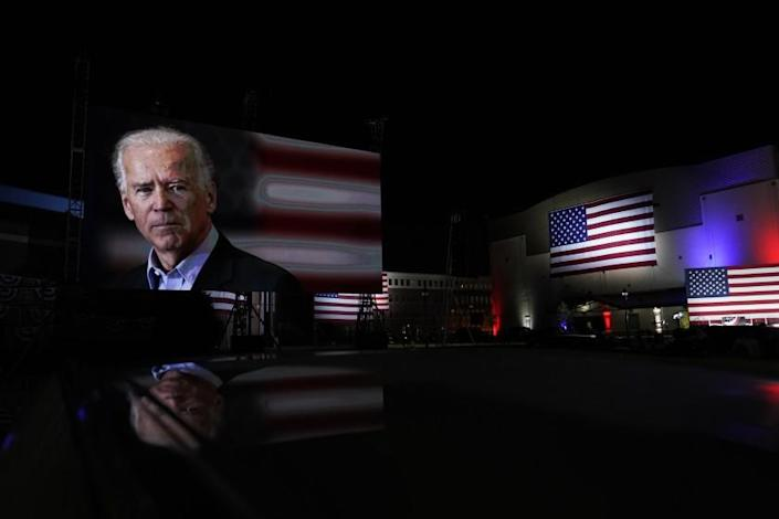 Images of Democratic presidential candidate former Vice President Joe Biden are shown on a screen outside the venue where Biden will speak later tonight, during the final day of the Democratic National Convention, Thursday, Aug. 20, 2020, at the Chase Center in Wilmington, Del. (AP Photo/Carolyn Kaster)