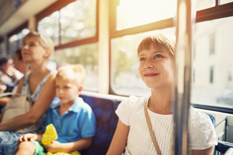 Smiling little girl aged 9 travelling by bus with mother and brother. They girl is smiling, summer sun is shining through the bus window. Mother and brother in the background.