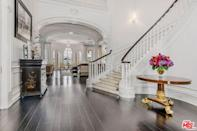 In the entry guests are greeted by a spiral staircase, beyond which are six bedrooms, eight bathrooms, a billiard room, and a four-car garage.