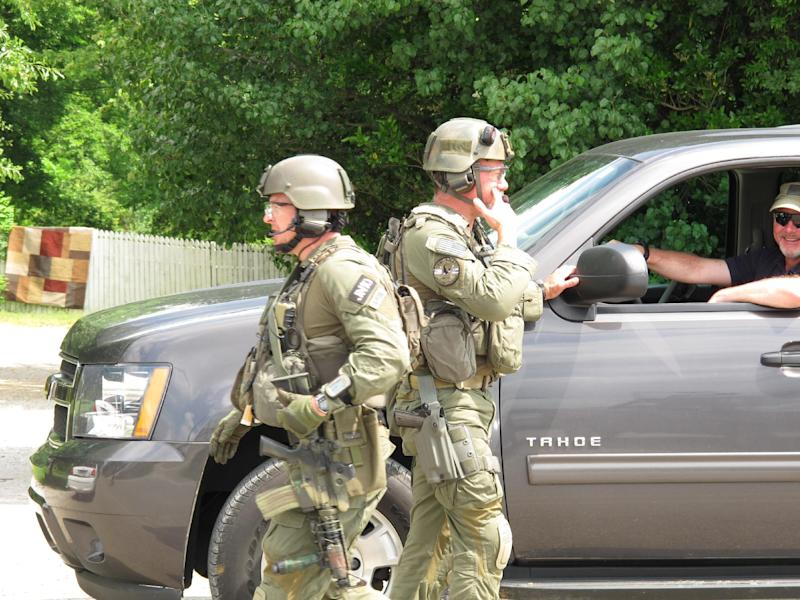 FBI agents get ready to resume their search for a man accused of abducting a Tennessee mother and her three daughters on Tuesday, May 8, 2012 in Guntown, Miss. Authorities on Tuesday  said they were searching for Adam Mayes 35, and two young girls, Alexandra Bain, 12, and Kyliyah Bain, 8. Teresa Mayes, 30, was charged with especially aggravated kidnapping and Mary Mayes, 65, was charged with conspiracy to commit kidnapping Tuesday,  (AP Photo/Adrian Sainz)