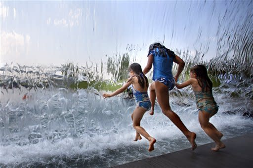 Girls leap through a wall of water at Yards Park in Washington, on Thursday, June 21, 2012. Heat index values are expected to exceed 100 degrees across the northeast on Thursday, according to the National Weather Service. (AP Photo/Jacquelyn Martin)