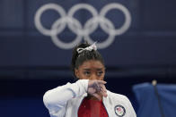Simone Biles, of the United States, watches gymnasts perform at the 2020 Summer Olympics, Tuesday, July 27, 2021, in Tokyo. Biles says she wasn't in right 'headspace' to compete and withdrew from gymnastics team final to protect herself. (AP Photo/Ashley Landis)