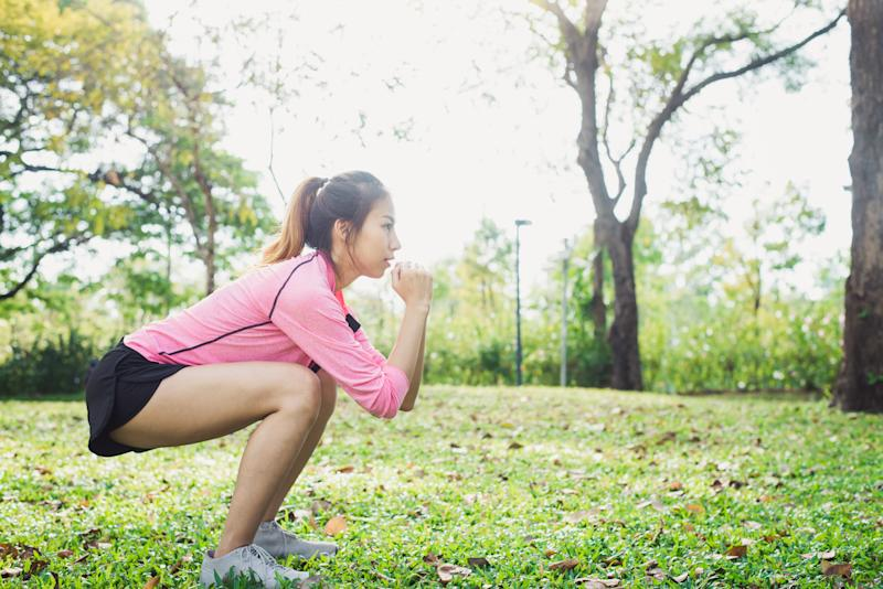 Young asian woman do squats for exercise to build up her beauty body in park environ with green trees and warm sunlight in the afternoon. Young woman workout exercise at the park. Outdoor exercising.