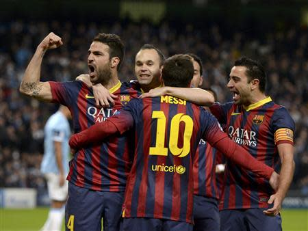 Barcelona players celebrate Lionel Messi's (BACK TO CAMERA) penalty against Manchester City during their Champions League round of 16 first leg soccer match at the Etihad Stadium in Manchester, northern England February 18, 2014. REUTERS/Nigel Roddis