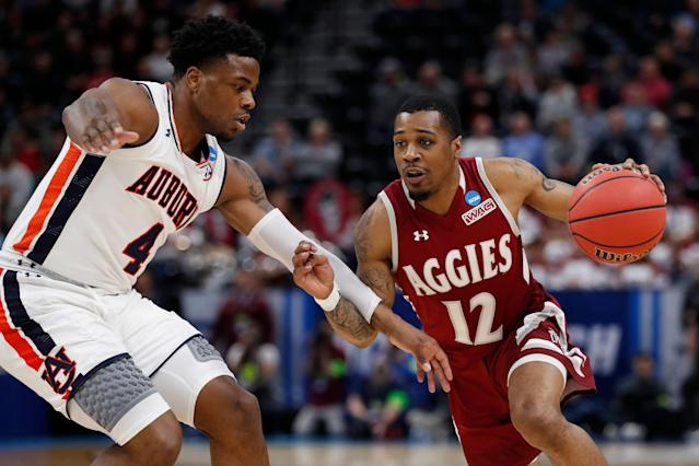 Auburn guard Malik Dunbar (4) defends New Mexico State guard AJ Harris (12) in the first half during a first round men's college basketball game in the NCAA Tournament Thursday, March 21, 2019, in Salt Lake City. (AP Photo/Jeff Swinger)