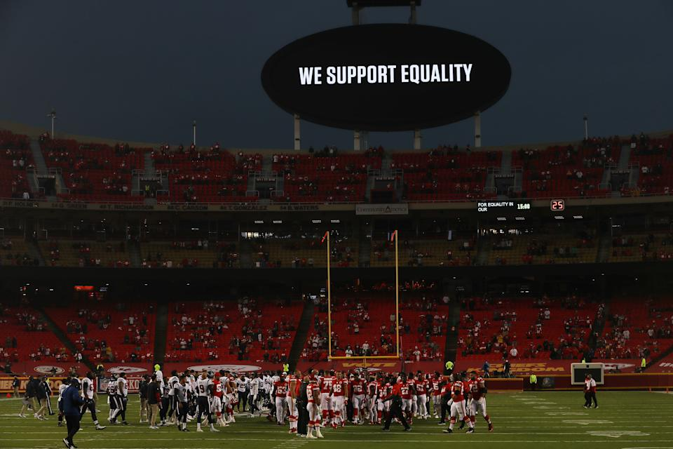 "Players from the Kansas City Chiefs and Houston Texans unite in a moment of silence in front of the video board that reads ""We support equality."""