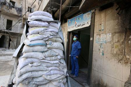 FILE PHOTO: A medic stands behind sandbags in the damaged al-Hakeem hospital, in the rebel-held besieged area of Aleppo, Syria November 19, 2016.   REUTERS/Abdalrhman Ismail/File Photo
