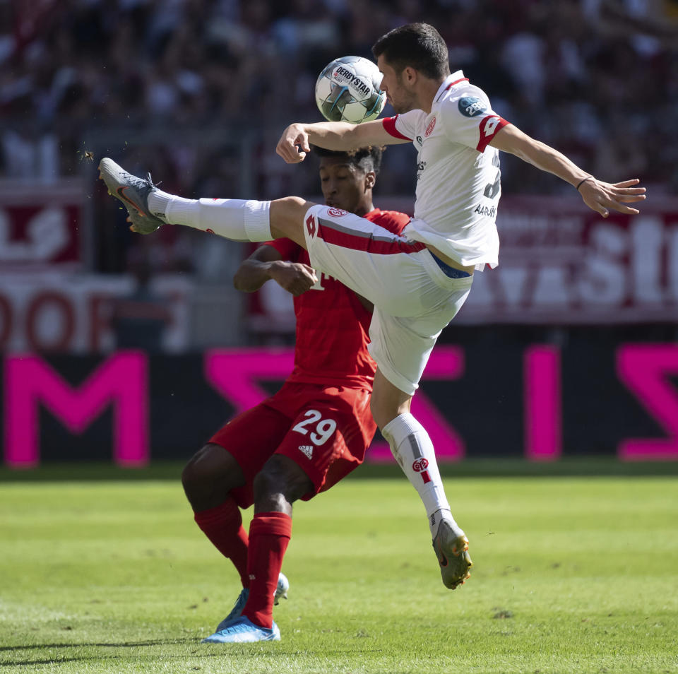 Munich's Kingsley Coman, left, and Mainz's Aaron Martin challenge for the ball during a German Bundesliga soccer match between Bayern Munich and FSV Mainz 05 in Munich, Germany, Saturday, Aug.31, 2019. (Sven Hoppe/dpa via AP)