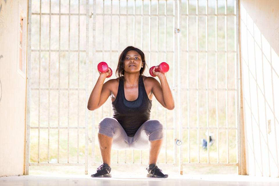<p>This full-body exercise gets your heart-rate up while toning the arms, legs, and glutes. </p><p><strong>How to: </strong>Stand tall with feet hip-width apart and hold a dumbbell in each hand with elbows bent so the weights are at shoulder height. Engage your core and push the booty back while keeping your chest lifted to lower down into a squat. Then, use your hips to propel your body back up and simultaneously press the weights straight overhead up to the ceiling so that your arms are fully extended. Then, lower the dumbbells back down to the starting position and repeat. </p>