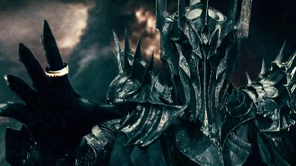 Sauron dressed in armor wears the One Ring during battle in a scene from The Lord of the Rings: The Fellowship of the Ring.