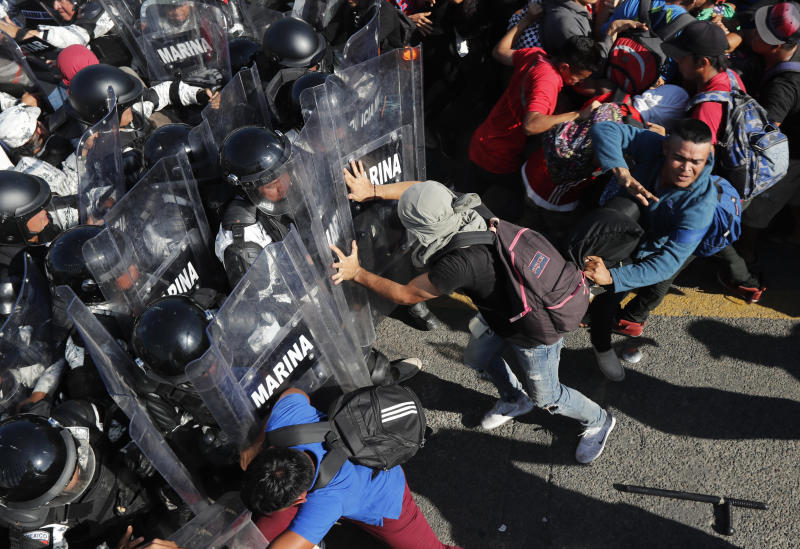 Migrants charge on Mexican National Guards at the border crossing between Guatemala and Mexico, near Ciudad Hidalgo, Mexico and Tecun Uman, Guatemala, Saturday, Jan. 18, 2020. More than a thousand Central American migrants surged onto a bridge spanning the Suchiate River that marks the border between both countries as Mexican security forces attempted to impede their journey north. (AP Photo/Marco Ugarte)