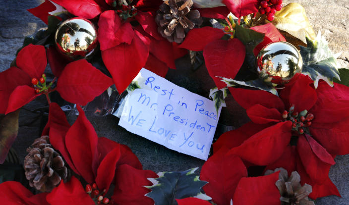 A wreath with a note to former President George H. W. Bush lay at a makeshift memorial across from Walker's Point, the Bush summer home, on Dec. 1, in Kennebunkport, Maine. (Photo: Robert F. Bukaty/AP)