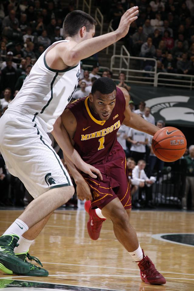 Minnesota's Andre Hollins (1) drives against Michigan State's Kenny Kaminski during the first half of an NCAA college basketball game, Saturday, Jan. 11, 2014, in East Lansing, Mich. (AP Photo/Al Goldis)