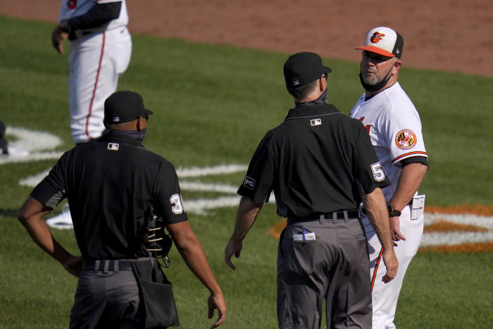 Baltimore Orioles manager Brandon Hyde, right, argues with umpire Dan Iassogna, center, and home plate umpire Jeremie Rehak after the Rehak ejected Hyde during the fourth inning of a baseball game, Thursday, April 8, 2021, on Opening Day in Baltimore. Hyde argued against a call on a pitch from Red Sox's Eduardo Rodriguez that hit Orioles' Rio Ruiz but wasn't awarded first base on a check swing strike. (AP Photo/Julio Cortez)
