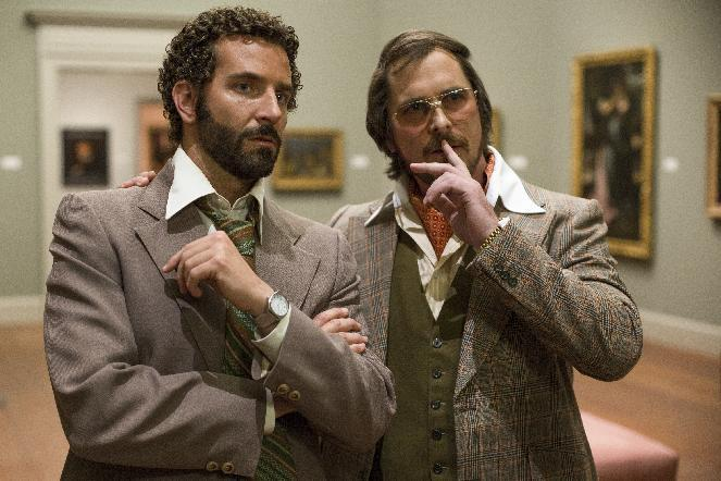 """This film image released by Sony Pictures shows Bradley Cooper, left, and Christian Bale in a scene from """"American Hustle."""" (AP Photo/Sony - Columbia Pictures, Francois Duhamel)"""