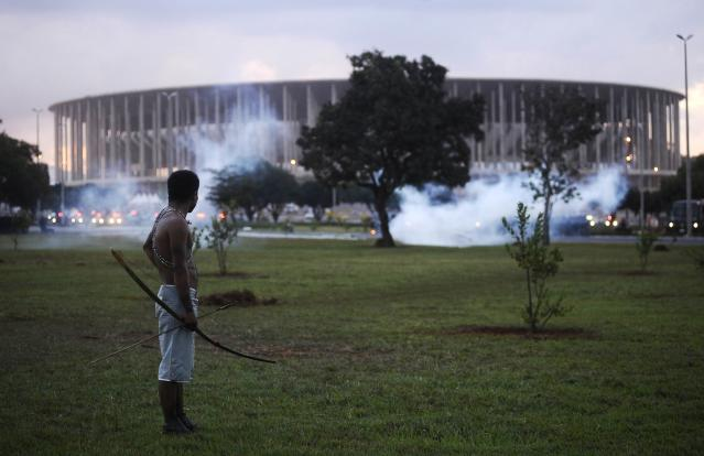 A native Brazilian stands in front of the Mane Garrincha soccer stadium as police use tear gas to impede a group of Indians from approaching it during a demonstration in Brasilia, May 27, 2014. Police fired tear gas canisters to contain anti-World Cup demonstrators who tried to march to the Brasilia stadium where the soccer tournament's trophy was on public display on Tuesday. REUTERS/Lunae Parracho (BRAZIL - Tags: SPORT SOCCER WORLD CUP CIVIL UNREST POLITICS TPX IMAGES OF THE DAY)