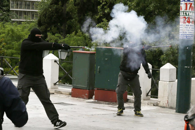 <p>Protesters aim with a flare gun to the riot police during clashes at a nationwide general strike demonstration, in Athens, May 17, 2017. Greek workers walked off the job across the country Wednesday for an anti-austerity general strike that was disrupting public and private sector services across the country. (Photo: Thanassis Stavrakis/AP) </p>