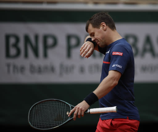 Lithuania's Ricardas Berankis wipes his face in his match against Serbia's Novak Djokovic in the second round of the French Open tennis tournament at the Roland Garros stadium in Paris, France, Thursday, Oct. 1, 2020. (AP Photo/Alessandra Tarantino)