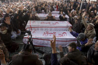 People from the Shiite Hazara community chant slogans beside caskets of coal mine workers who were killed by unknown gunmen near the Machh coal field, during a sit-in protest, in Quetta, Pakistan, Monday, Jan. 4, 2021. Gunmen opened fire on a group of minority Shiite Hazara coal miners after abducting them, killing 11 in southwestern Baluchistan province early Sunday, a Pakistani official said. (AP Photo/Arshad Butt)