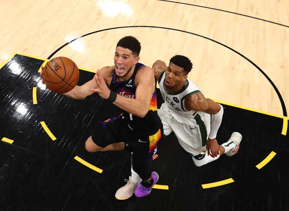 An overhead view of Devin Booker driving to the basket with Giannis Antetokounmpo trailing him.