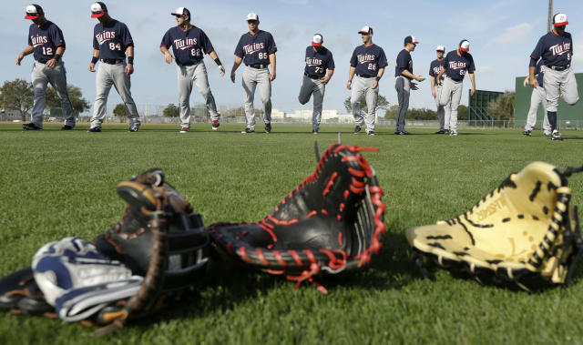Minnesota Twins players warm up on the field during spring training baseball practice Friday, Feb. 21, 2014, in Fort Myers, Fla. (AP Photo/Steven Senne)