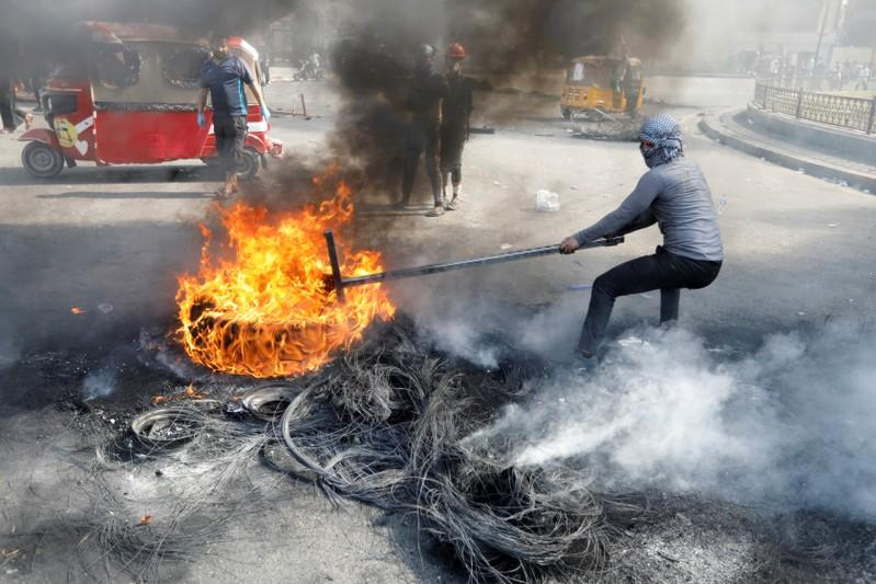 An Iraqi demonstrator pulls a burnt tire as he blocks the road during ongoing anti-government protests, in Baghdad