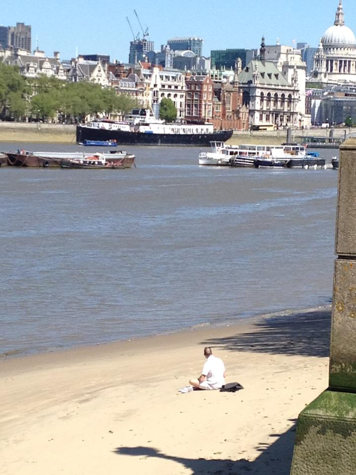 London's Southbank in summer - man sunbathes on beach by Waterloo Bridge
