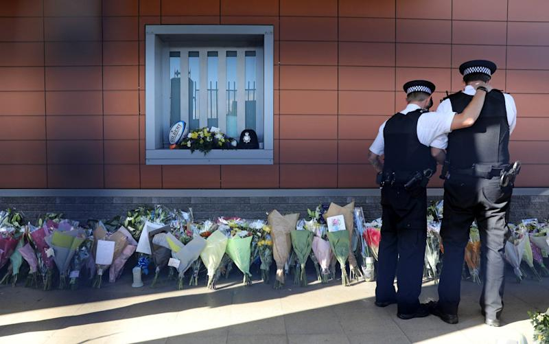 Police officers are seen at the custody centre where a British police officer has been shot dead in Croydon, south London - REUTERS