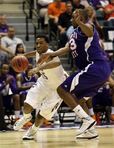 Stephen F. Austin's Desmond Haymon, left, drives toward the basket as Northwestern State's James Hulbin, right, defends during the first half of a Southland Conference championship basketball gameon Saturday, March 16, 2013, in Katy, Texas. (AP Photo/David J. Phillip)