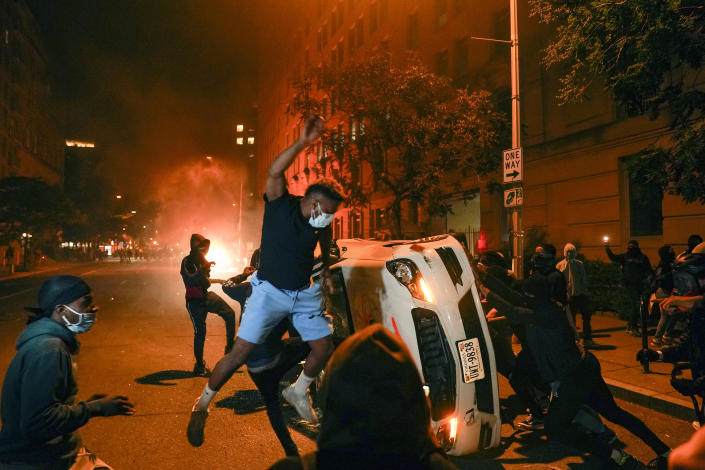 Demonstrators vandalise a car as they protest the death of George Floyd on Sunday. (AP Photo/Evan Vucci)