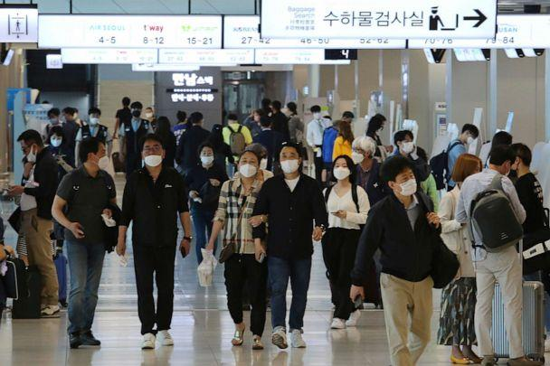 PHOTO: People wearing face masks arrive at the domestic flight terminal of Gimpo International Airport in Seoul, South Korea, on May 27, 2020. South Korean authorities now require all airplane passengers to wear masks amid the coronavirus pandemic. (Ahn Young-joon/AP)