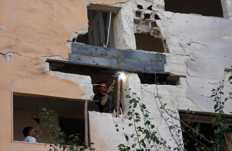 Worker fixes the damage to a building from an Israeli attack in Damascus
