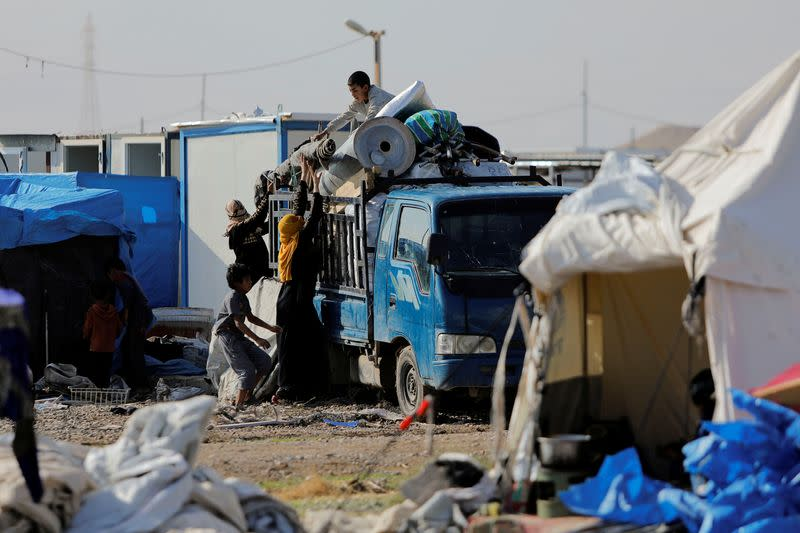 Displaced Iraqis load their belongings onto a truck as they prepare to be evacuated, at Hammam Al-Alil camp, south of Mosul,