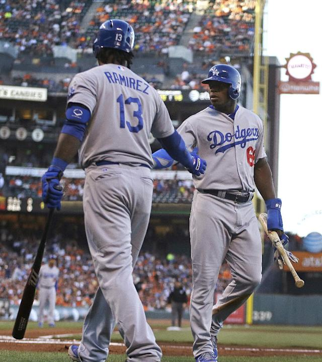 Los Angeles Dodgers' Yasiel Puig, right, is congratulated by Hanley Ramirez after Puig scored against the San Francisco Giants in the first inning of a baseball game Friday, July 25, 2014, in San Francisco. Puig scored on a single by Adrian Gonzalez. (AP Photo)