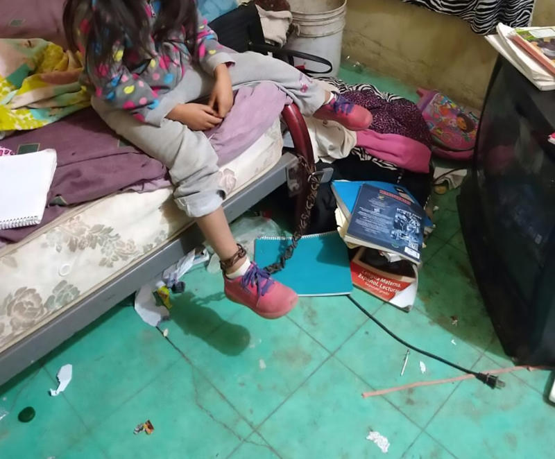 A five-year-old Mexican girl is seen here chained to a bed after neighbours heard screams believed to be from her.