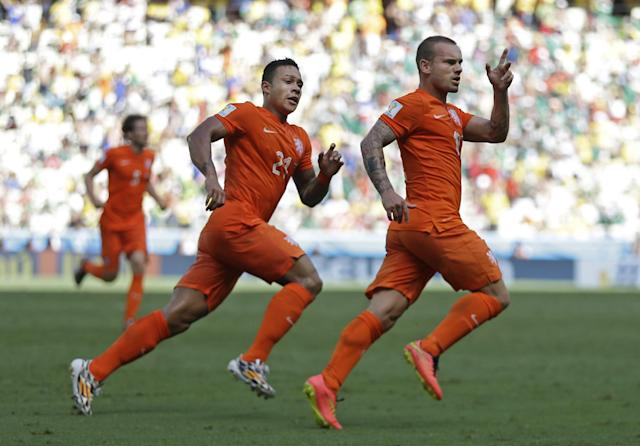 Netherlands' Wesley Sneijder, right, celebrates after scoring his side's first goal during the World Cup round of 16 soccer match between the Netherlands and Mexico at the Arena Castelao in Fortaleza, Brazil, Sunday, June 29, 2014. (AP Photo/Natacha Pisarenko)