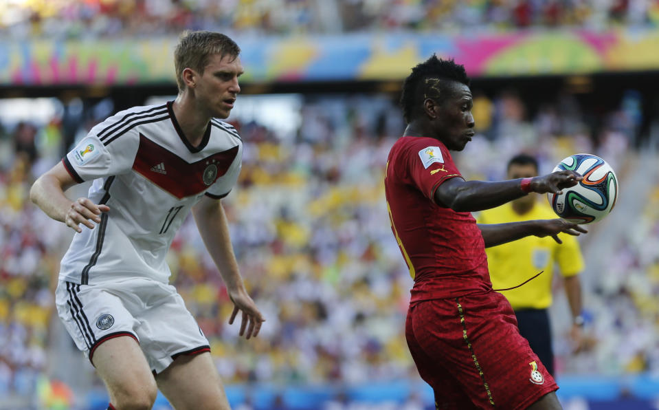 Germany's Per Mertesacker, left, closes down Ghana's Asamoah Gyan during the group G World Cup soccer match between Germany and Ghana at the Arena Castelao in Fortaleza, Brazil, Saturday, June 21, 2014. (AP Photo/Matthias Schrader)