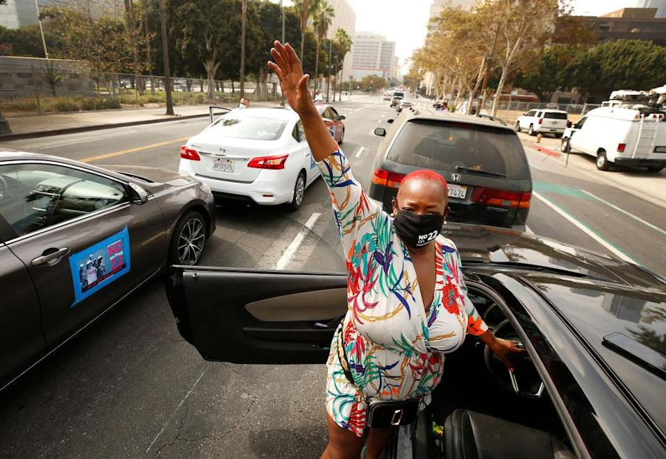 LOS ANGELES, CA - OCTOBER 08: Latasha Houston, who has been a Lyft driver for three years takes video as she honks her horn in support as app based gig workers held a driving demonstration with 60-70 vehicles blocking Spring Street in front of Los Angeles City Hall urging voters to vote no on Proposition 22, a November ballot measure that would classify app-based drivers as independent contractors and not employees or agents, providing them with an exemption from Californias AB 5. The action is part of a call for stronger workers rights organized by the Mobile Workers Alliance with 19,000 drivers in Southern California and over 40,000 in all of California. Los Angeles on Thursday, Oct. 8, 2020 in Los Angeles, CA. (Al Seib / Los Angeles Times