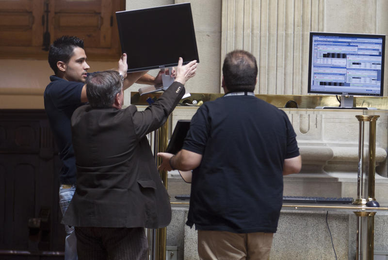 Workers try to get a screen working at the Stock Exchange in Madrid Monday July 23, 2012. The Bank of Spain says the country's recession-plagued economy contracted 0.4 percent in the second quarter, a performance even worse than in the first three months of the year.The central bank blamed a big drop in domestic demand: minus 1.2 percent compared to minus 0.5 percent in the first quarter as household and government spending fell at a faster pace. It stressed that these figures were preliminary. (AP Photo/Paul White)