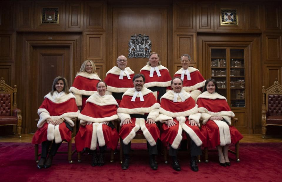 Nine judges in red and white robes pose for a photo.
