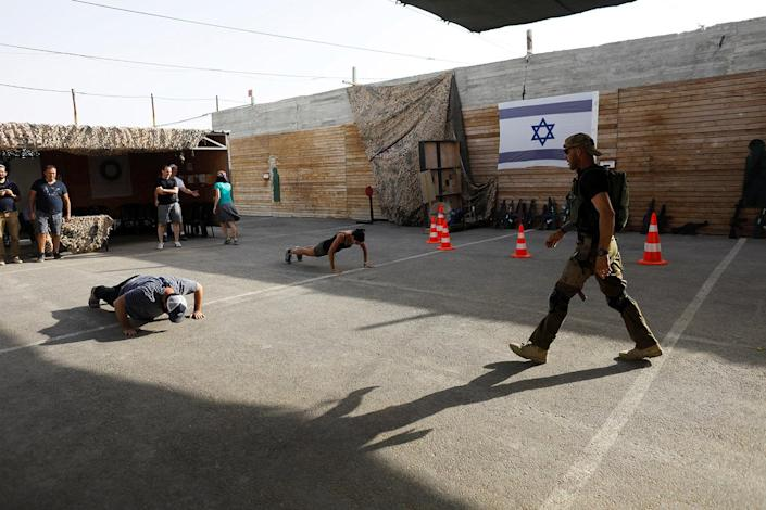 "<p>An Israeli instructor walks near tourists as they take part in a two hour ""boot camp"" experience, at ""Caliber 3 Israeli Counter Terror and Security Academy"" in the Gush Etzion settlement bloc south of Jerusalem in the occupied West Bank July 13, 2017. (Photo: Nir Elias/Reuters) </p>"