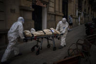 Mortuary workers carry the body of an elderly person who died of COVID-19 after removing it from a nursing home in Barcelona, Spain, Friday, Nov. 13, 2020. (AP Photo/Emilio Morenatti)