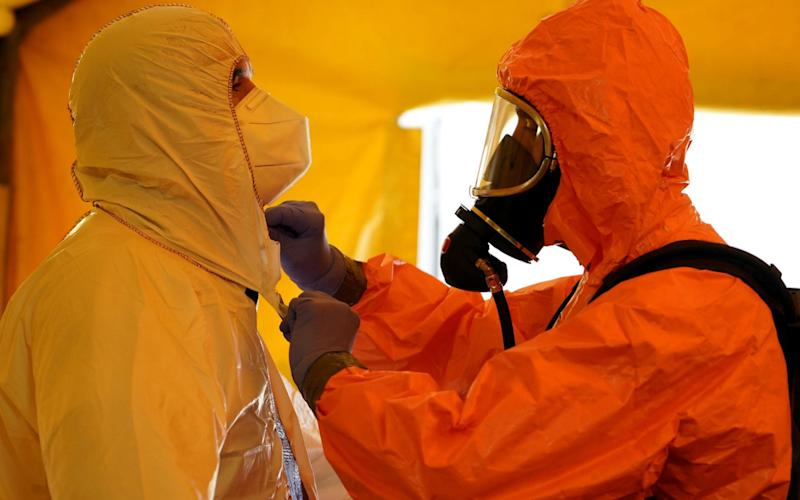 A member of Madrid's SAMUR Ambulance Service adjusts protective gear of his colleague at their headquarters in Madrid - JUAN MEDINA/REUTERS