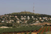 The Israeli village of Metulla, background, is seen from the Lebanese-Israeli border, in the village of Kfar Kila, in southeast Lebanon, Wednesday, May 20, 2020. Twenty years after Hezbollah guerrillas pushed Israel's last troops from southern Lebanon, both sides are gearing up for a possible war that neither seems to want. (AP Photo/Bilal Hussein)